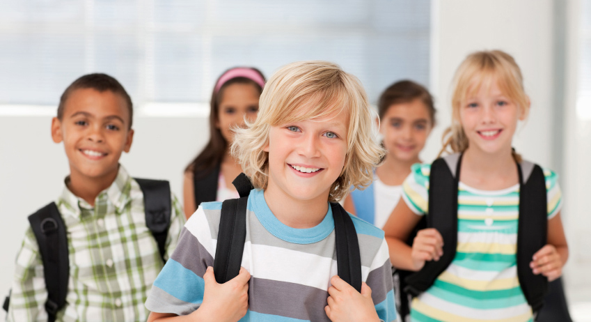 Portrait of a happy school boy carrying his bag , group of friends at the back